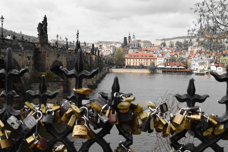 Charles Bridge on the Vltava river with a lot of love locks on a railing let by tourists. Selective color effect applied. Stock Photo - 93848887