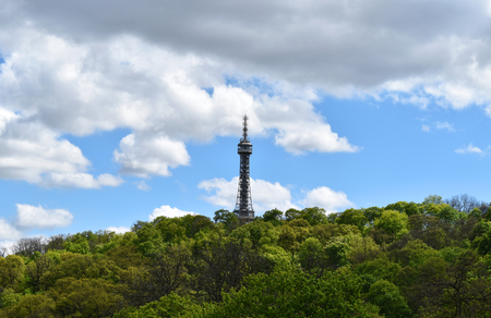 A metal tower in a green forest with blue sky and white clouds. Stock Photo - 93865247