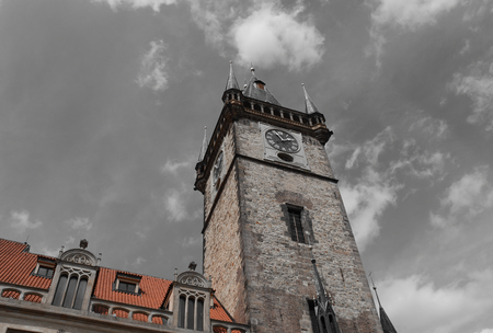 The clock tower of Old Town Hall in Prague, Czech Republic, with blue sky and white clouds in the background. Selective Color applied.