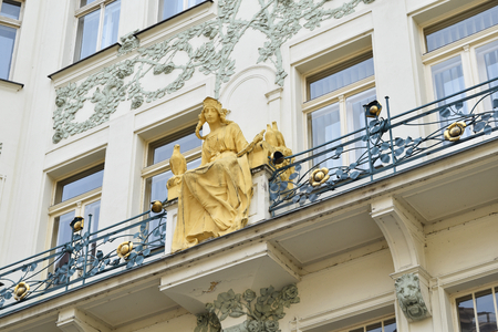 An old golden statue of a young woman in a terrace of an ancient white palace in Prague in Czech Republic. Stock Photo - 94105442
