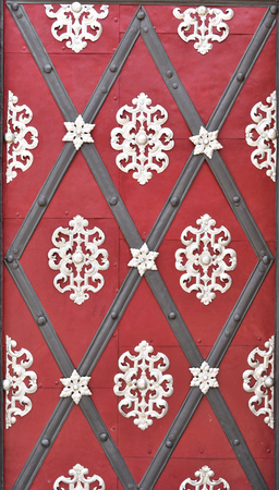 A very old red door with metal grey and white arabesques and diamonds; suitable to be used like background. Stock Photo - 93848903