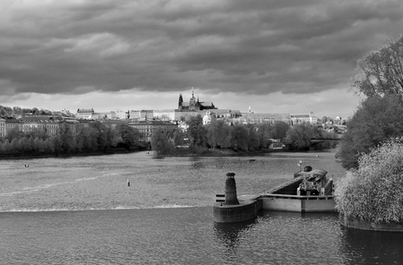 View of the city center of Prague in Czech Republic, seen by the bank of the river Vltava. Black and white. Stock Photo - 94105476