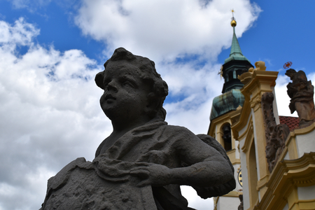 A grey old statue of a angel with, in the background, the convent of Loreto in Prague in Czech Republic in a sunny day with blue sky. Stock Photo - 93848908