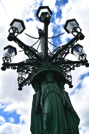An ancient and big lamppost in Castle square in Prague, in Czech Republic, with blue sky and white clouds in the background, decorated with statues and lanterns. Stock Photo - 94105449