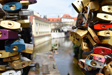 Close up of many colorful love locks let by tourists on a railing with a canal in the background. Stock Photo - 93848912