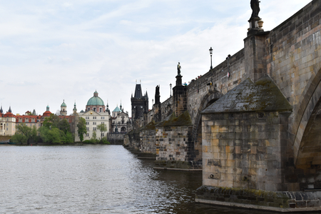 A view of Charles Bridge on the Vltava river and the city center in Prague in Czech Republic in a cloudy day. Stock Photo - 94108514