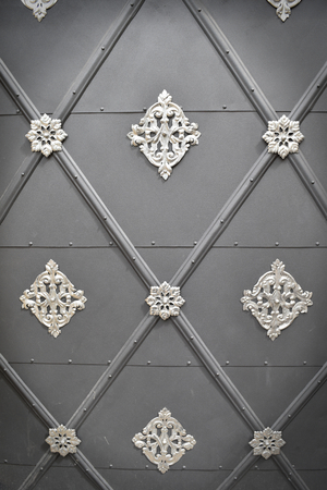 A very old metal grey door with white arabesques and diamonds; suitable to be used like background. Vignette effects applied. Stock Photo - 94077978