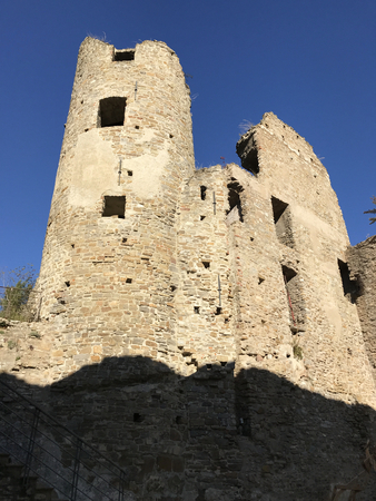 The Medieval ruined castle of Dolceacqua in Italy with blue sky in the background.