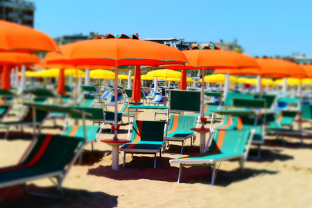 A beach full of umbrellas and beach loungers but without people. Tilt-shift effect applied.