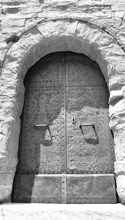 An old metal door in a stone wall