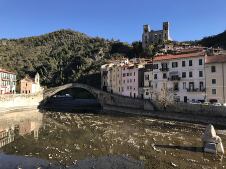 A view of the Medieval ancient town of Dolceacqua in Italy with its ruined castle, the old stone bridge and torrent Nervia. Stock Photo