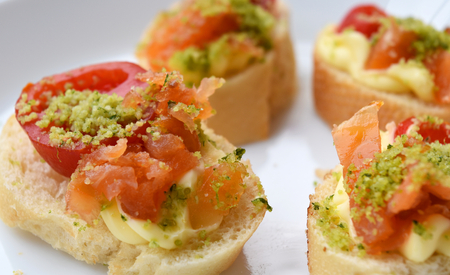 Homemade canapès with salmon, tomato and bread. Stock Photo