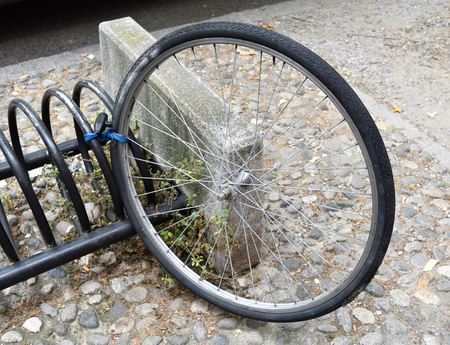 RAVENNA, ITALY, JULY 2016: Strange theft of bicycle: the thief leaves the wheel tied to the bike rack.
