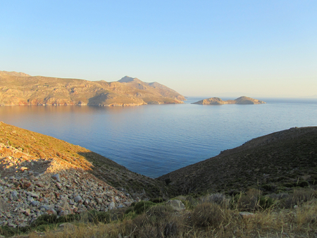 The coast of Tilos island with blue sea and big stack at sunrise, Greece Stock Photo