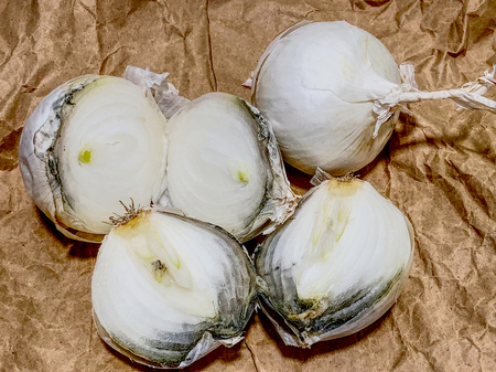 White onions with grey mold on brown paper background.