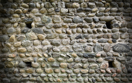 Background of a ancient wall made with pebbles stones. Vignette effect applied.