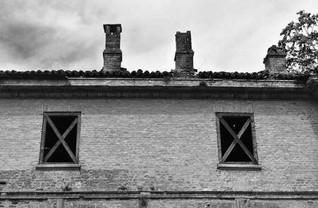Abandoned and ruined buildings of the ancient damaged Cittadella of Alessandria in Italy. Black and white. Stock Photo