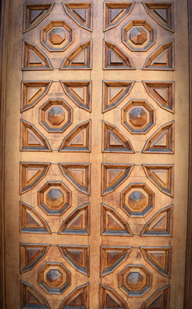 A wooden door with geometric decorations. Vignette effect. Stock Photo