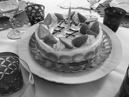 To celebrate birthday with a traditional Italian cake with whipped cream and strawberry. Black and white.