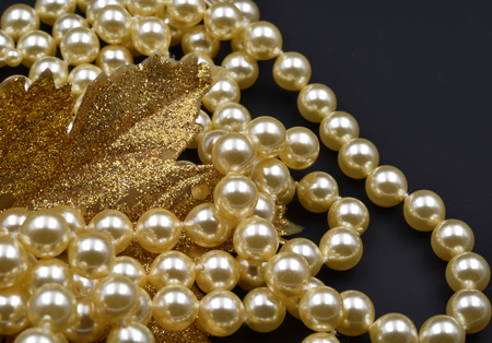 Pearls and glittering golden leaf with black background. Stock fotó
