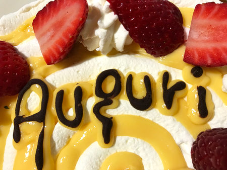 """""""Auguri"""" (""""best wishes"""") written with chocolate on a traditional Italian cake with whipped cream and strawberry for celebrate birthday. Stock Photo"""