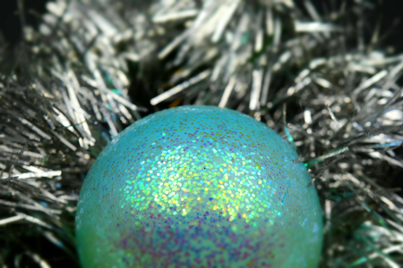 Christmas tree decorations: a glittering turquoise bauble and sparkling silver ribbons. Tilt-shift effect applied. Stock Photo