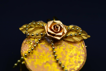 A handmade little golden box with beads, leaves and a rose. Black background. Tilt-shift effect applied. Stock Photo