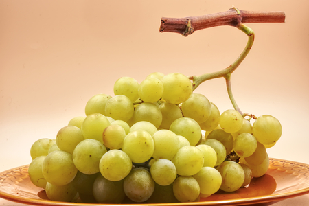 Bunch of white green grapes with light orange background. HDR effect.