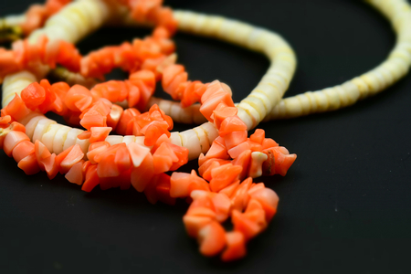 Necklaces of red pink and white Bamboo Coral with black background. Tilt-shift effect applied.
