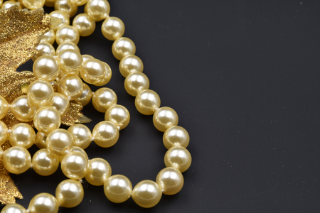 Pearls and glittering golden leaf with black background. Copy space. Stock Photo
