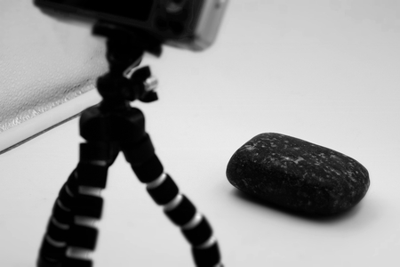 Defocused background of a digital camera on a small tripod in a soft box taking a photo of a stone. Intentionally blurred post production for bokeh effect. Concept for photography. Black and white. Stock Photo