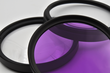 Concept for modern digital photography tools: two transparent lens filter and one purple. On white background. Banco de Imagens