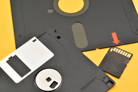 Very old 5¼-inch and 3½-inch floppy disk and a modern memory card. Old and modern technology on yellow background.