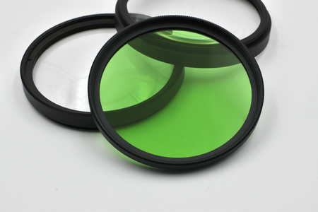 Concept for modern digital photography tools: macro of two transparent lens filter and one green. On white background.