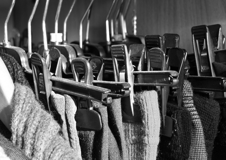 Many clothes hanging in a full closet. Black and white.