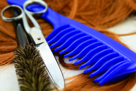 Concept for hairdresser: scissors, blue comb, brush and a lock of copper hair. Tilt-shift effect applied.