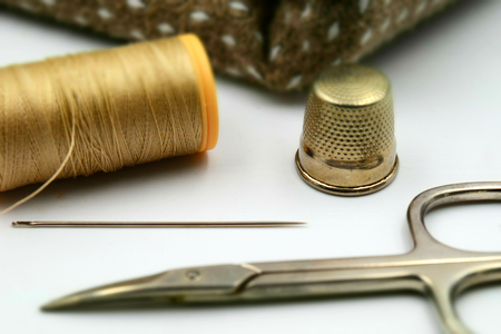 Concept for sewing: needle, thimble, scissors, thread, cloth on white background. Tilt-shift effect applied.