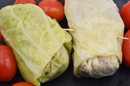 Two Italian homemade Capunet: typical Piedmont Savoy cabbage rolls with meat inside. Fresh tomatoes in the background.
