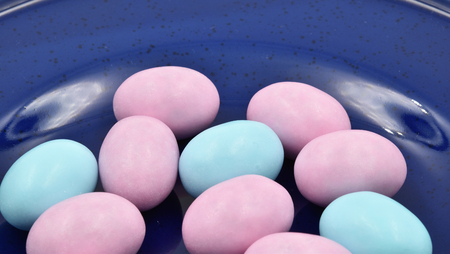 Close up of pastel pink and turquoise Easter eggs on a blue plate. Suitable to be used like a background.