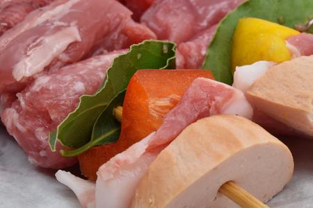 Meat skewers with sausage, pork, beef, peppers and laurel leaf