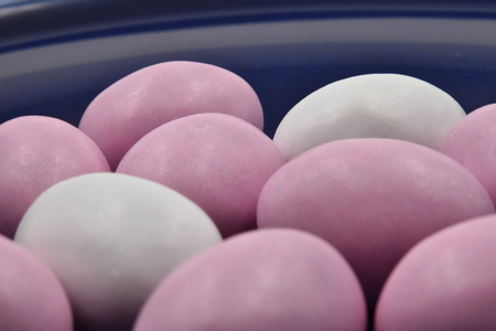 Close up of pastel pink and white Easter eggs on a blue plate. Suitable to be used like a background. Stock Photo