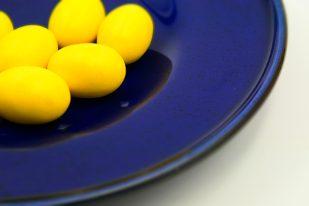 Close up of pastel yellow Easter eggs on a blue plate. Suitable to be used like a background. Tilt-shift effect applied.
