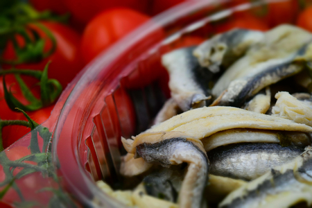 Homemade Italian anchovies in oil with fresh tomatoes in the background. Tilt-shift effect applied.