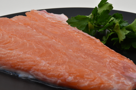 A raw fillet of salmon with its pink meat and some green parsley Stock Photo