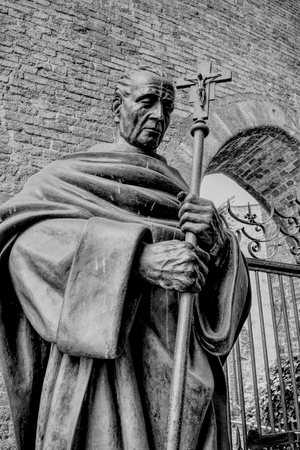 An ancient statue of an old saint with a cross near an Italian church. HDR effect and black and white.