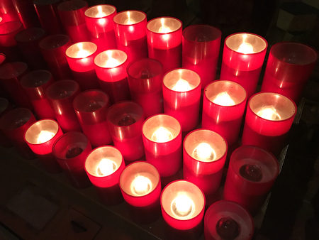 Many electrical plastic red votive candles in a dark church on black background. Stock Photo