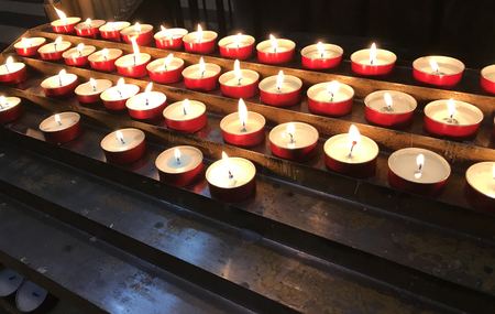 Many little votive wax red candles with flames in a dark church.