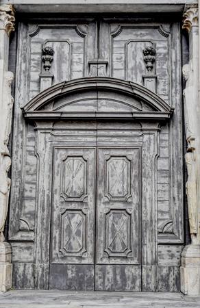 A big ancient Medieval grey wooden door.