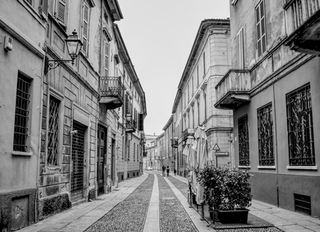 An almost empty street in Cremona in Italy with houses and buildings. Black and white.