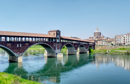 The Ponte Coperto (Covered Bridge) on river Ticino and the city of Pavia, Italy. HDR effect.